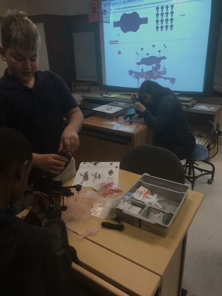 Middle schoolers assembling drones